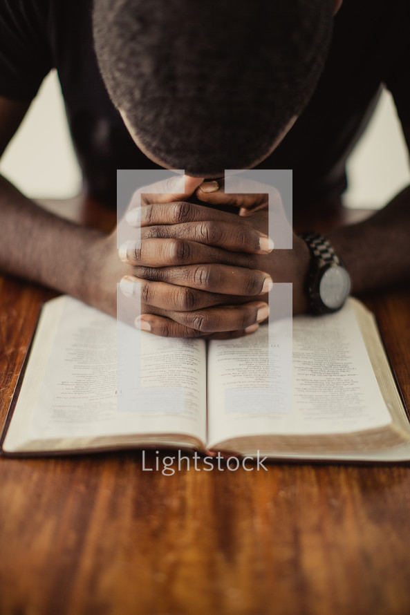 man praying over a Bible