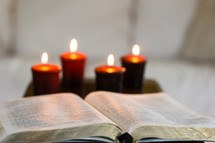 open Bible and burning candles