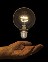 A shining light bulb floating above a person's hand.