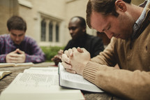 A group of men praying during a Bible study