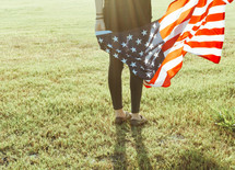 a woman holding an American flag standing in grass