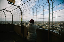 A woman standing on a roof of a building looking out at the view of a city