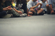 Kids sitting on ground with legs crossed.