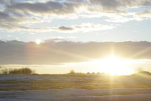 sunrise over a snow covered field on a farm