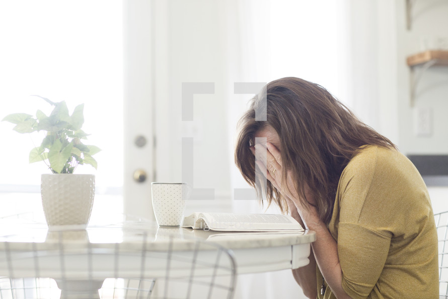 a woman crying with an open Bible on a kitchen table
