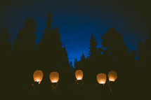 about to release paper lanterns into the night sky