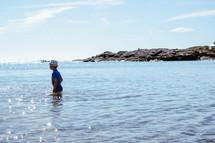 a little boy walking into the ocean water