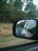 road in a car mirror