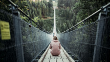 a woman sitting on a swinging bridge