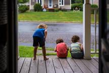 children sitting on a front porch