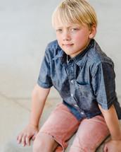 a boy child sitting on a curb