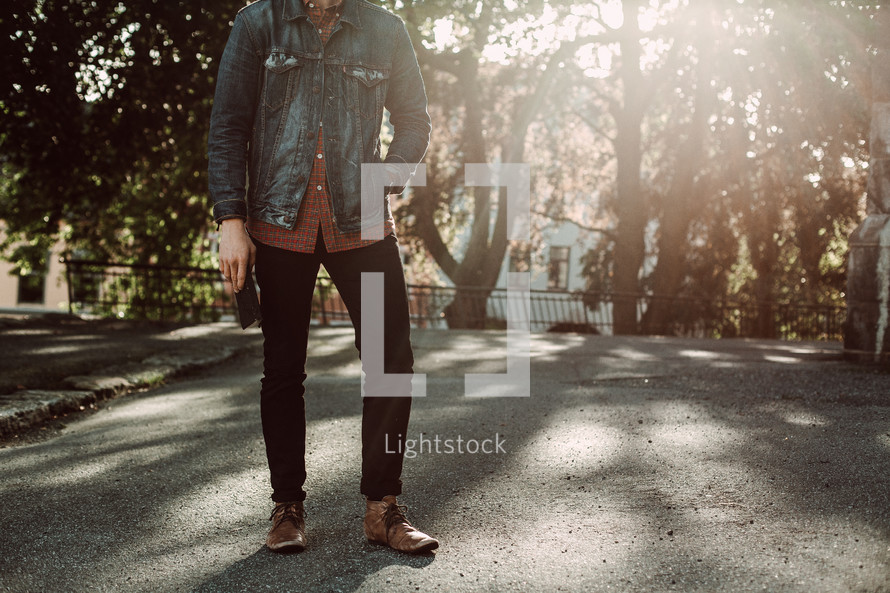 legs of a young man holding a Bible