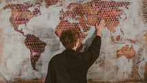 a man with his hands on a world map painted on burlap