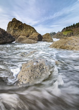 tide flowing through rocks onto a shore