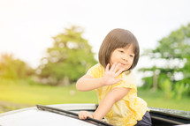 toddler girl waving out of a sunroof