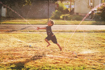 boy playing in a sprinkler