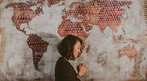 A woman praying in front of a world map
