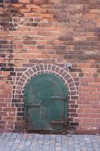 green metal door on a brick wall