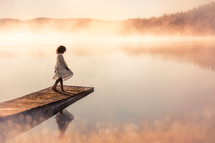 girl on a dock over a steaming lake at sunrise