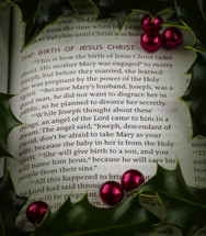 Close-up Christmas scripture Birth of Christ, Matthew 1:18-21 with holly and berries