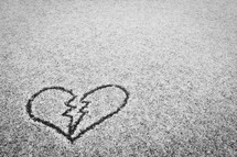 broken heart drawn in the snow on pavement
