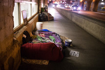 homeless sleeping bags on a city sidewalk