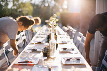 peeple setting up a table for a dinner party