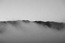 fog rising over a mountain