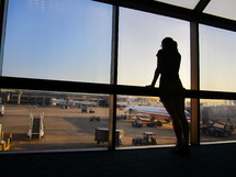 woman looking out airport windows at the terminal and runway