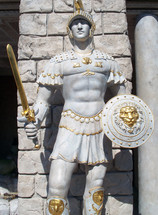 A life sized statue of a Roman guard with full battle armor, shield, sword and helmet adorned in gold accent to show the detail of what a roman soldier would look like during ancient Rome during the time of Christ.