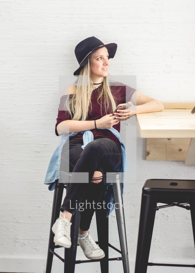 a young woman sitting on a stool holding a cellphone