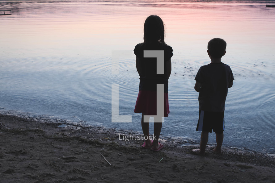 children standing in front of a lake at sunset