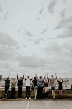 people standing on a rooftop parking deck with hands raised