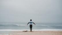 a surfer standing on a beach