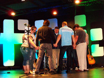 The pastors and staff at a local church gather together to have a word of prayer before the morning worship church service begins. Here, a group of seven pastors, worship leaders and musicians gather together in a circle holding hands and asking God to bless the time of worship and morning music and sermon. They are standing on a sound stage surrounded by guitars, drums, keyboards, microphone stands and lighted stage for the morning worship celebration.