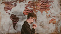 a man praying in front of a world map