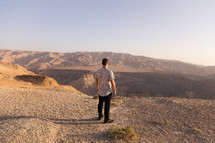 a man looking out at a desert landscape