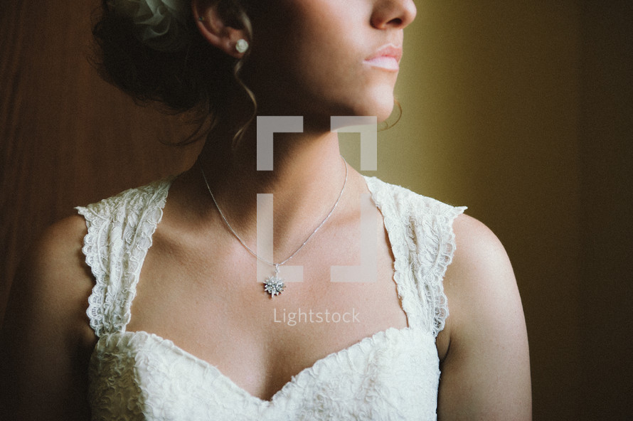 View of a bride's necklace and dress; neck down