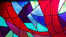 A colorful stained glass window with crimson red, violet, purple, aquamarine blue, navy blue and multiple colors in a church sanctuary window.