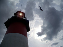 An old and sturdy white and red striped light house juts out off the coast to be a light to ships at sea who are in need of safe harbor and protection from the storms at sea while a Hawk flies overhead against an evening sunset off the coast of the sea.