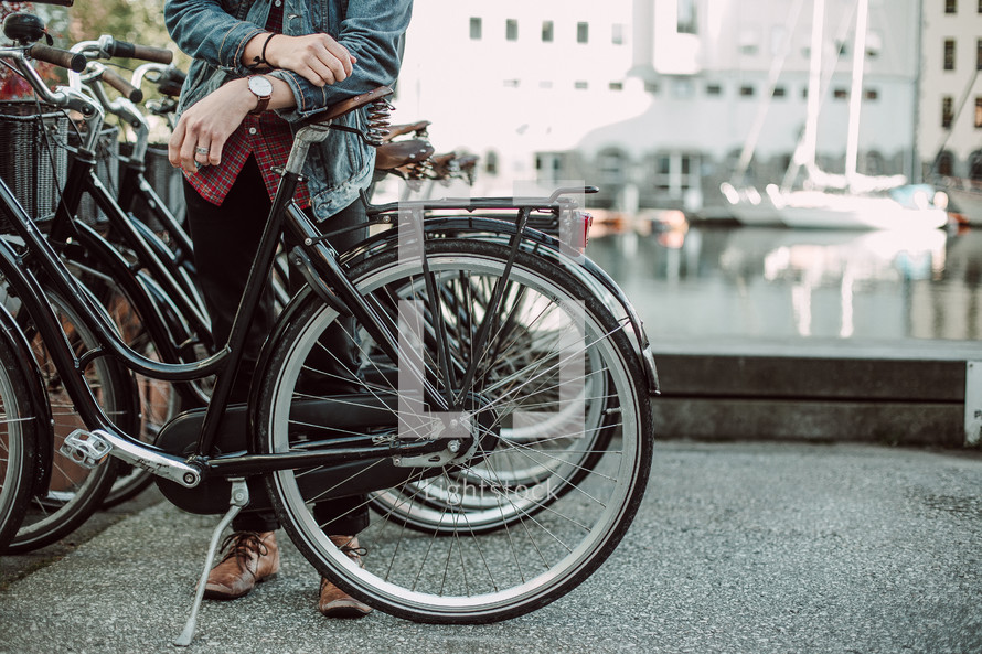 a young man in a jean jacket leaning against bikes in a bike rack