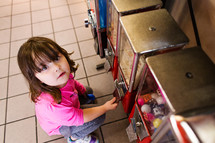 a child getting a toy out of a vending machine