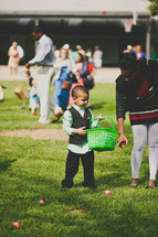 child with a basket during an Easter egg hunt