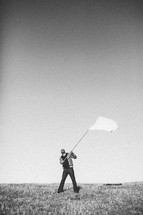 Man in field waving white flag.