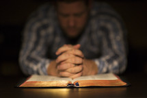 A man praying over an open Bible.