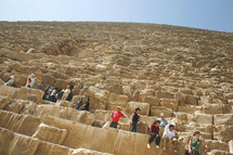 people sitting on the sides of the pyramids in Egypt