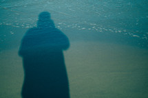 shadow of a man standing over the tide