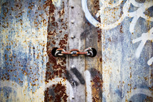 rusty chain and graffiti on metal