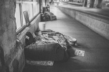 homeless sleeping bags on a city sidewalk at night