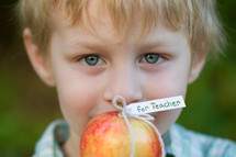 child holding an apple for the teacher